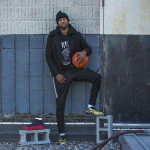 Man holding basketball standing next to basketball shoe cover