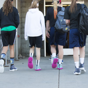 Basketball players walking in to gym with basketball shoe covers