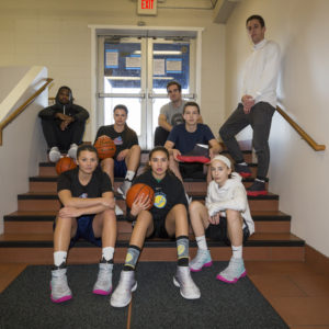 Basketball players in stairwell holding basketballs and shoe covers