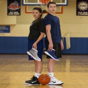 Basketball players holding their basketball shoe covers