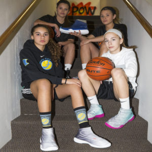 Friends in stairwell holding basketball shoe covers