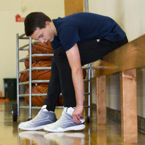 Guy putting on his basketball shoe covers on the basketball court