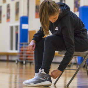 Girl putting on FY-DENY basketball shoe cover