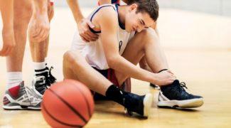 Young basketball player holding his leg in pain.